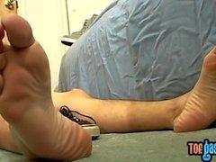 Junger Mann Bentley, der an seinen hübschen Füßen zerrt und spritzt