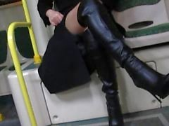 La muchacha en las medias y botas de cuero negro destellantes en bus