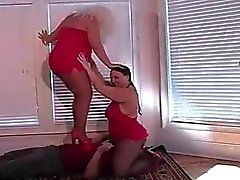 Two fat chicks are stomping on a dude and squishing his pri