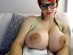 Sensual redhead displays her humongous breasts for your ple