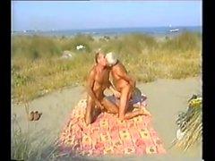 Seyirciler ile tabaklanmış plajda babalar