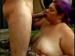 donna Chunky con i capelli viola cade in ginocchio e soffia un grosso cazzo