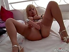 Mature British slut fucks her pierced pussy with a big dildo