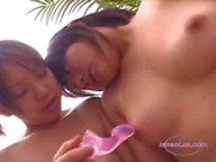 2 meninas asiáticas estimulando seus mamilos com brinquedos no sofá