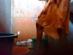 Jungen Bangladesh guy halten ein versteckte Nocken in der bathroom vor der