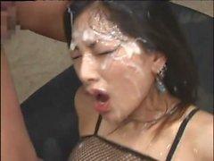 Seductress asiático en la ropa interior del fishnet goza de una ducha de la semilla en una sesión del bukkake