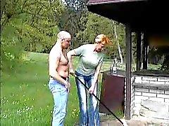 Mummo perseestä ja ratsastaa kukko nurmikolla Park