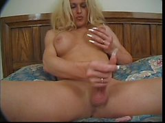 Busty blonde tranny lays in bed and strokes her enormous cock then toys her ass