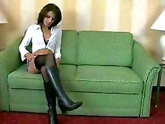 Amateur Brunettefrau in Stiefeln und schwarzen Nylons macht einen Kerl auf einer grünen Couch