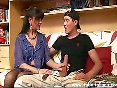Brunette Italiaanse MILF geeft een jongere jongen een blowjob op de bank