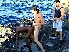 Schwarze Küken saugt weiße Schwänze und wird am Strand gefickt