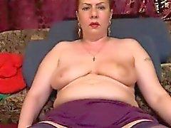 Stor breasted mogen kvinna som i strumpor sveper sina läppar aroun