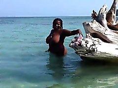 Grasa bebé negro wades desnudo en las aguas poco profundas y juega con h