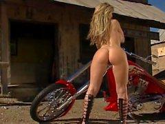 Blonde sexy do motociclista que têm o divertimento