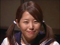 Muchacha asiática de la universidad en uniforme tiene su cara rayada en jugo del schlong en una fiesta del bukkake
