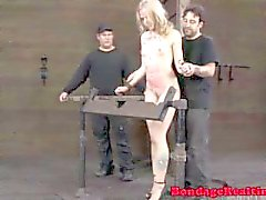 Humiliated sub held in wooden stocks