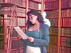 Young blonde schoolgirl and busty brunette librarian play with a strapon in the library